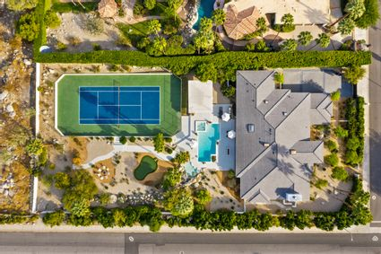 aerial shot of property with pool, tennis court, and golf course